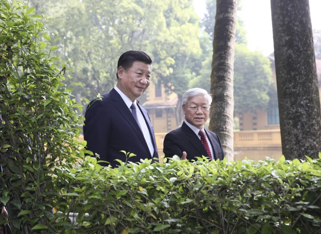 Visiting Chinese President Xi Jinping, who is also general secretary of the Communist Party of China (CPC) Central Committee, and Nguyen Phu Trong, General Secretary of the Communist Party of Vietnam (CPV) Central Committee, go for a stroll at the former residence of late Vietnamese leader Ho Chi Minh in Hanoi, Vietnam, November 13, 2017. [Photo: Xinhua/Lan Hongguang]