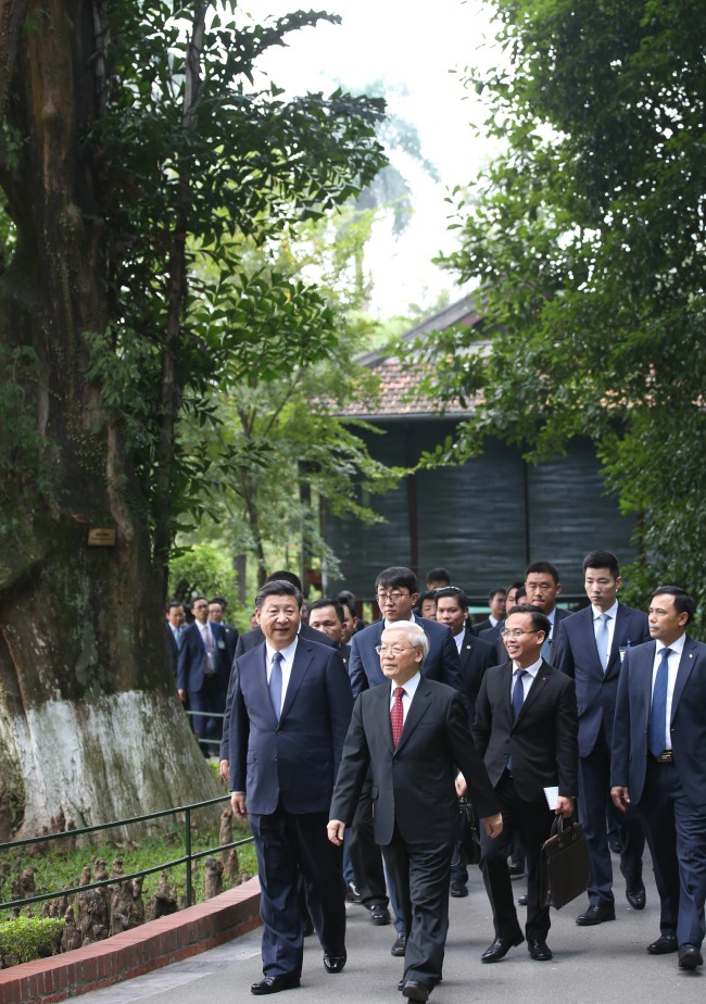 Visiting Chinese President Xi Jinping, who is also general secretary of the Communist Party of China (CPC) Central Committee, and Nguyen Phu Trong, General Secretary of the Communist Party of Vietnam (CPV) Central Committee, go for a stroll at the former residence of late Vietnamese leader Ho Chi Minh in Hanoi, Vietnam, November 13, 2017. [Photo: Xinhua/Yao Dawei]