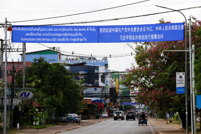 "Banners bearing welcome slogans in the Chinese and Lao languages ""Warmly welcome the state visit by Comrade Xi Jinping, general secretary of the CPC Central Committee and Chinese president, to Laos,"" are seen hanging on the main streets in Vientiane, November 13, 2017. [Photo: China Plus/Tu Yun]"