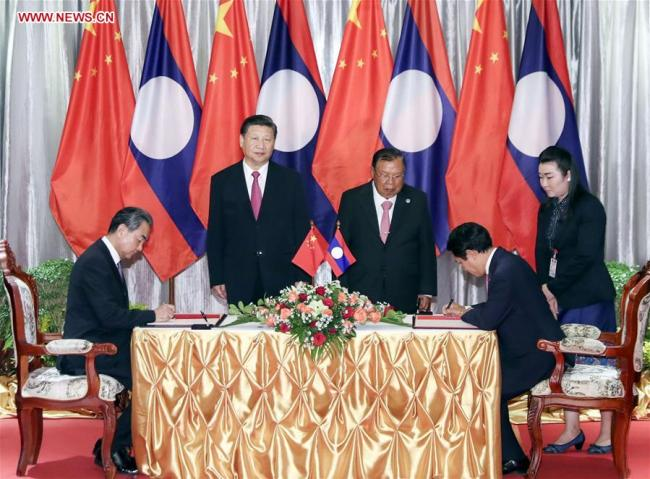 Chinese President Xi Jinping (L rear), also general secretary of the Communist Party of China Central Committee, and Lao President Bounnhang Vorachit (C rear), also general secretary of the Lao People's Revolutionary Party Central Committee, witness the signing of a deal to enhance cooperation under new circumstances between the two countries after meeting again in Vientiane, Laos, Nov. 14, 2017. [Photo: Xinhua]