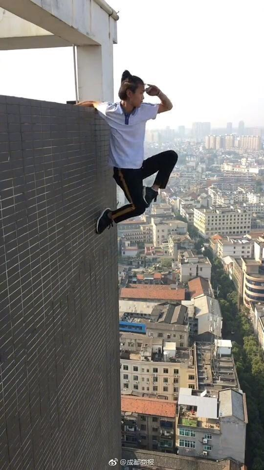"""Wu makes a """"Monkey King"""" gesture with one hand clinging to the edge of a high building. [Photo: sina.cn]"""