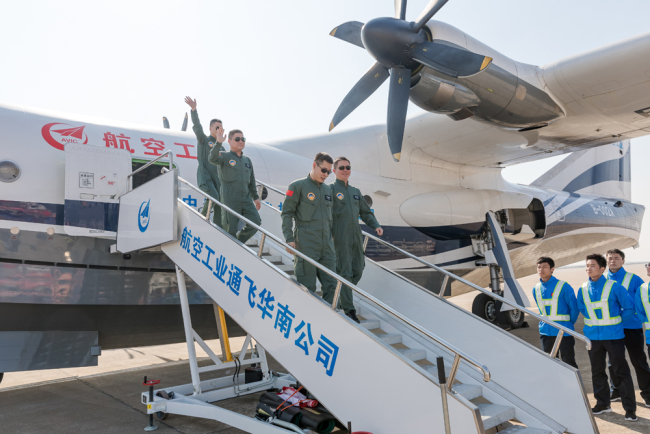 The crew members wave after China's first domestic large amphibious aircraft AG600 completed its maiden flight and landed at the Jinwan Civil Aviation Airport in the city of Zhuhai, Guangdong Province, on Sunday, December 24, 2017. [Photo: China Plus/Li Jin]