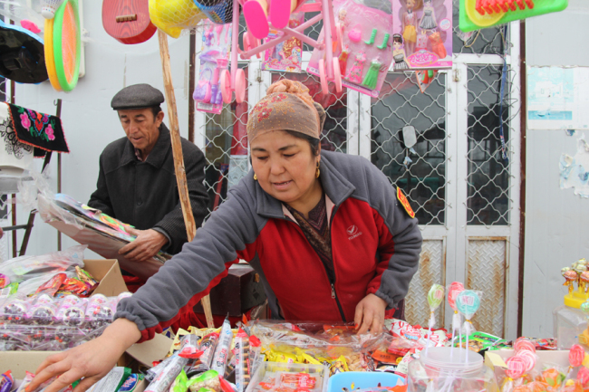 Turshunjan Sawut helps his wifi organize the toy goods they sell in their store on November 19th. [Photo: China Plus/Yang Guang]