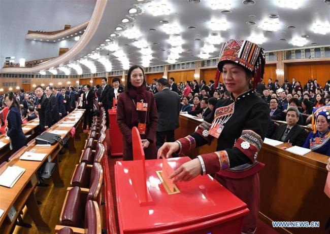 A deputy to the 13th National People's Congress (NPC) casts her ballot on a draft amendment to the country's Constitution at the third plenary meeting of the first session of the 13th NPC in Beijing, capital of China, March 11, 2018. [Photo: Xinhua]