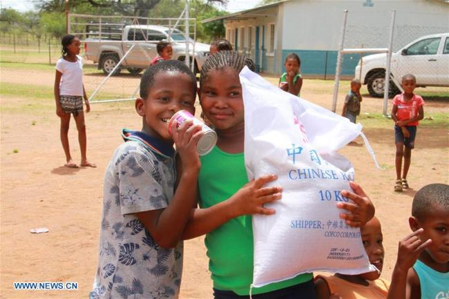 Children carry a bag of rice in Dordabis farm, Khomas Region, central Namibia, on Jan. 11, 2017. The first batch of China Aid Food was distributed at Dordabis farm on Jan. 11, 2017. [Photo: Xinhua]