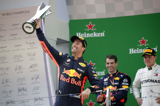 Red Bull driver Daniel Ricciardo of Australia raises his trophy as he celebrates after winning the Chinese Formula One Grand Prix at the Shanghai International Circuit in Shanghai, Sunday, April 15, 2018. At right is Mercedes driver Valtteri Bottas of Finland who finished second.[Photo: AP]