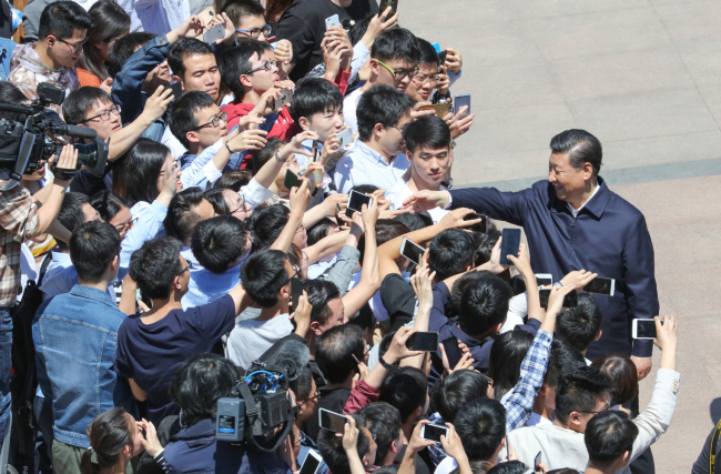 Chinese President Xi Jinping shakes hands with students during his visit to Peking University in Beijing, on May 2, 2018. [Photo: Xinhua]