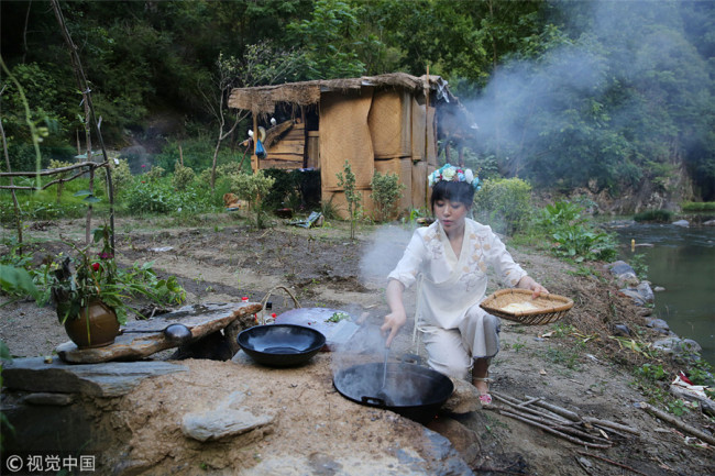 Zhang Fang cooks beside a brook in Shiquan county, Ankang city, Shaanxi province, June 4, 2018. [Photo/VCG]