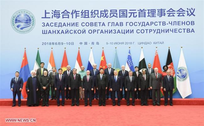 Chinese President Xi Jinping (6th R, front) poses for a group photo with other leaders and guests ahead of the 18th Meeting of the Council of Heads of Member States of the Shanghai Cooperation Organization (SCO) in Qingdao, east China's Shandong Province, June 10, 2018.[Photo: Xinhua]