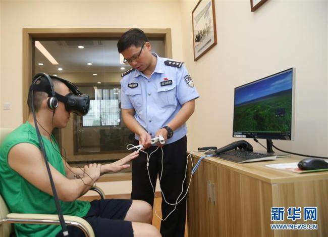 A police officer helps a patient wearing VR devices on June 20, 2018, at Shanghai Qingdong rehabilitation center. [Photo: Xinhua]