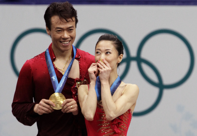 China's Shen Xue, right, kisses her gold medal as Zhao Hongbo, left, looks on, after they won the pairs free program figure skating competition at the Vancouver 2010 Olympics in Vancouver, British Columbia, Monday, Feb. 15, 2010.[Photo:AP]