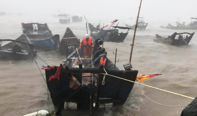Firefighters use a boat to evacuate a stranded fisherman off Lianjiang county of Fujian province's capital, Fuzhou, on Wednesday. [China Daily]