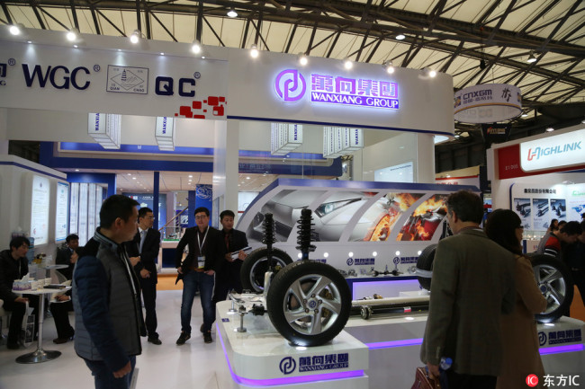 People visit the stand of Wanxiang Group during the 2014 Automechanika Shanghai (AMS) exhibition in Shanghai,December 9, 2014. [Photo: IC]