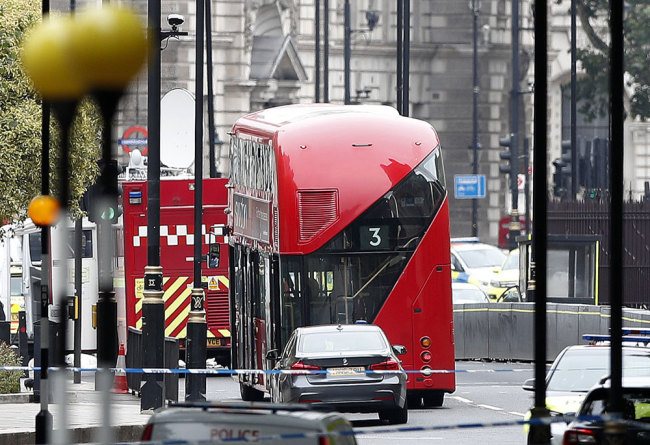 A car that crashed into security barriers outside the Houses of Parliament stands to the right of a bus in London, Tuesday, Aug. 14, 2018. [Photo: AP/Alastair Grant]