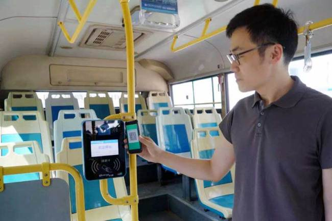 A passenger uses his smartphone to scan a QR code to pay his bus fare in the Beijing suburbs on Wednesday, September 12, 2018. [Photo: Beijing Morning Post]