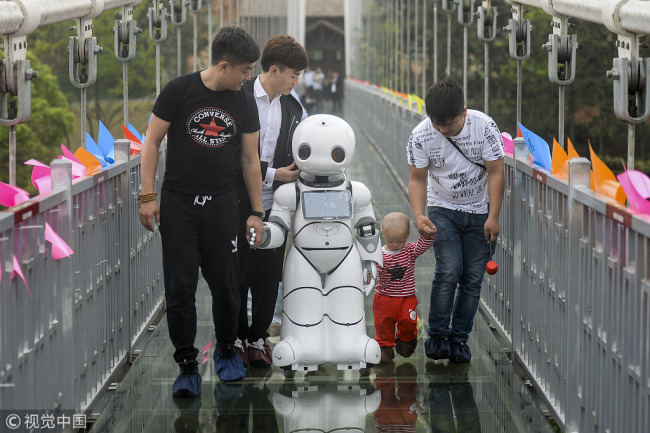 A robot guides tourists along a glass bridge above Shiyan Lake in Changsha, Hunan Province on April 4, 2018. [Photo: VCG]