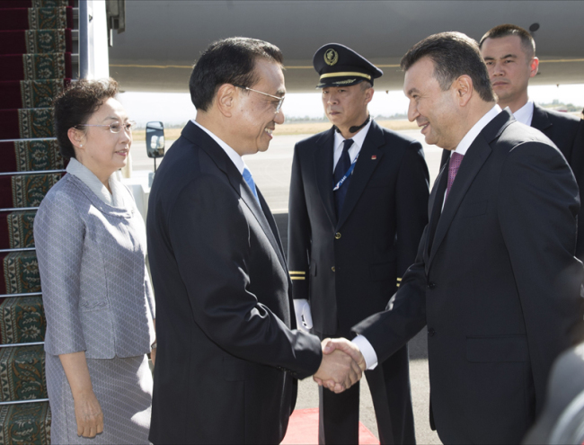 Chinese Premier Li Keqiang shakes hands with Tajikistan Prime Minister Kokhir Rasulzoda as he arrives at the Dushanbe international airport on Thursday, October 11, 2018. [Photo: gov.cn]