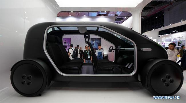 Visitors watch a new electric vehicle at the first China International Import Expo (CIIE) in Shanghai, east China, Nov. 6, 2018. The first CIIE is held from Nov. 5 to 10 in Shanghai. [Photo: Xinhua/Wang Jianhua]