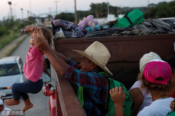 A migrant, part of a caravan traveling en route to the United States, helps a child to board a truck, as they hitch a ride on the truck, in Santo Domingo Ingenio, Mexico, on November 8, 2018. [Photo: VCG]