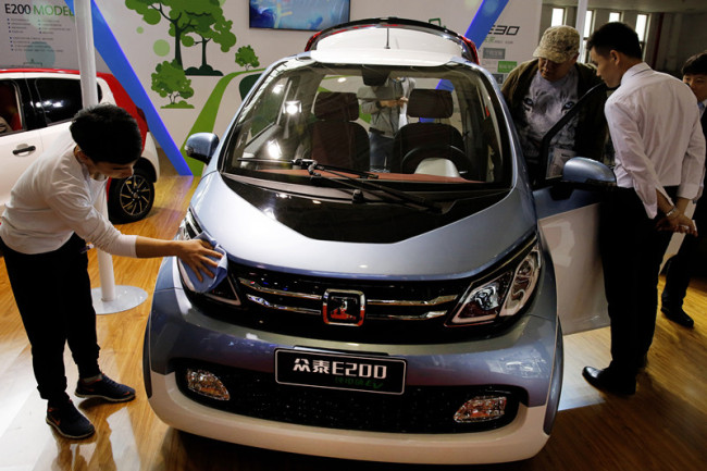 Visitors to the Beijing International Automotive Exhibition look at the Chinese automaker Zotye Auto's E200 electric vehicle displayed in Beijing, Tuesday, April 26, 2016. [Photo: AP/Andy Wong]