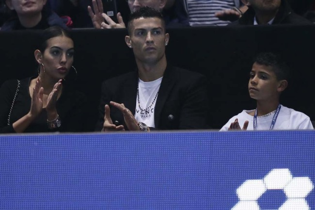 Cristiano Ronaldo, center, with his partner Georgina Rodriguez, and his son Cristiano Ronaldo Jr watches as Novak Djokovic of Serbia plays John Isner of the United States in their ATP World Tour Finals singles tennis match at the O2 Arena in London, Monday Nov. 12, 2018. [Photo: AP]