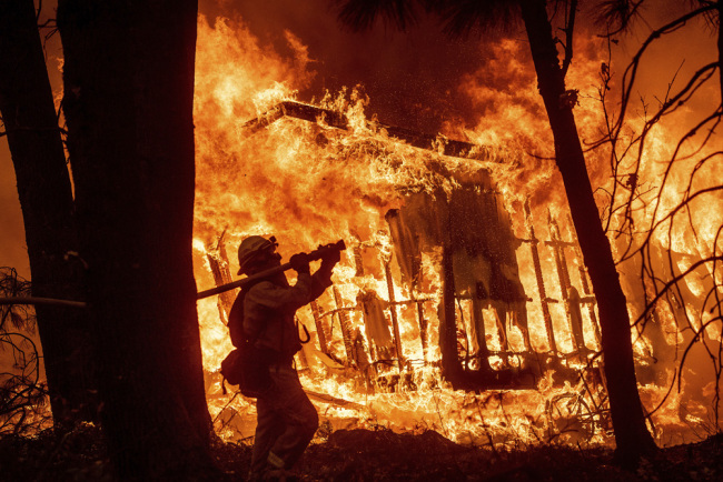 In this Nov. 9, 2018 file photo, firefighter Jose Corona sprays water as flames from the Camp Fire consume a home in Magalia, Calif. A massive new federal report warns that extreme weather disasters, like California's wildfires and 2018's hurricanes, are worsening in the United States. [Photo: AP]