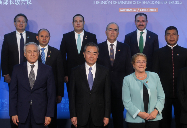 (Front L-R) Chile's Foreign Minister Heraldo Munoz, China's Foreign Minister Wang Yi and Chilean President Michelle Bachelet pose for the family picture of the Second Ministerial Meeting of the Forum of China and the Community of Latin American and Caribbean States (China-CELAC) in Santiago, on January 22, 2018. [Photo: AFP/CLAUDIO REYES]