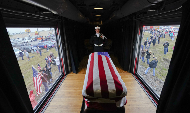 The flag-draped casket of former President George H.W. Bush passes through Magnolia, Texas, Thursday, Dec. 6, 2018, along the route from Spring to College Station, Texas. [Photo: AP/David J. Phillip]