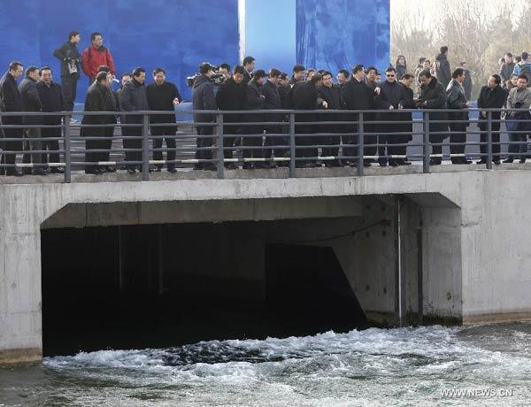People watch the opening of a sluice gate of the middle route of the south-to-north water diversion project in Beijing, capital of China, Dec 27, 2014.[Photp:Xinhua]