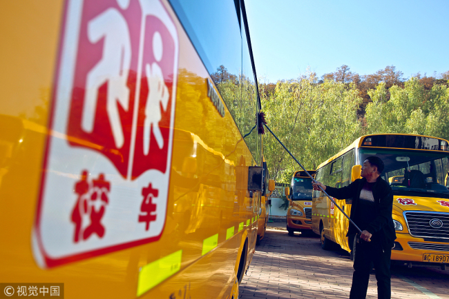 A bus driver cleans a school bus in Huachangyu village, Hebei Province, October 18 2018. [Photo: VCG]