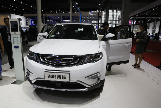 A visitor looks at a SUV from Chinese automaker Geely during the Auto Shanghai 2017 show at the National Exhibition and Convention Center in Shanghai, China, Wednesday, April 19, 2017. Models on display at Auto Shanghai 2017, the global industry's biggest marketing event of the year, reflect the conflict between Beijing's ambitions to promote environmentally friendly propulsion and Chinese consumers' love of hulking, fuel-hungry SUVs. [Photo: AP]