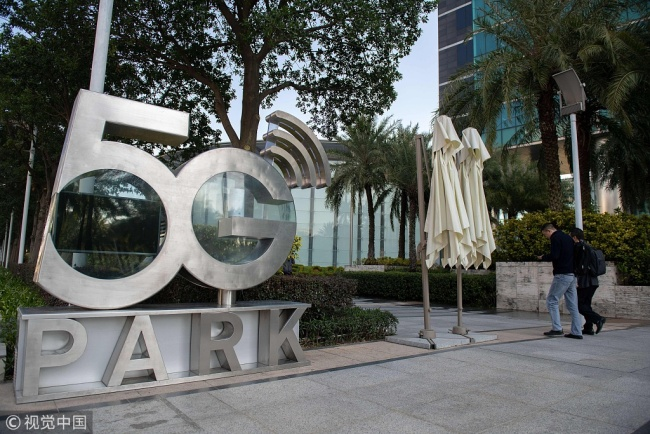 """People walk past a sign that reads """"5G park"""" inside the Huawei global headquarters in Shenzhen on December 18, 2018. [Photo: VCG]"""