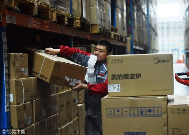 A courier sorts parcels at a warehouse in Hangzhou, Zhejiang Province on November 12, 2018. [Photo: VCG]
