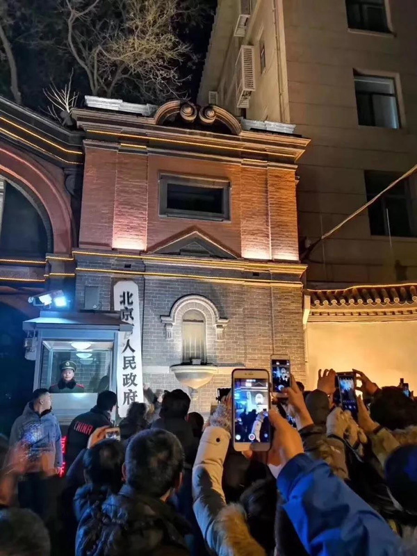 Residents take pictures of the original plaque of Beijing Municipal Government as it is removed from the government offices' former site and sent to the Beijing Municipal Archives for storage on Jan 10, 2019. [Photo: CCTV]