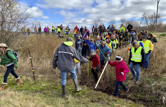 In this Oct. 23, 2018, file photo, volunteers cross a creek and barbed wire near Barron, Wis., on their way to a ground search for 13-year-old Jayme Closs who was discovered missing Oct. 15 after her parents were found fatally shot at their home. [File photo: AP/Jeff Baenen]