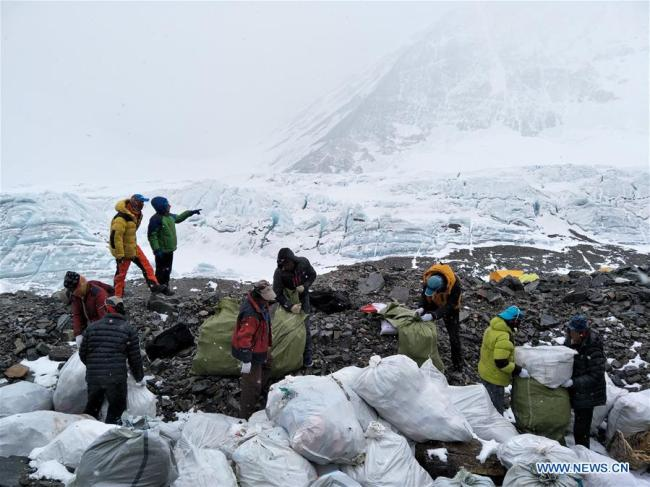 People collect wastes at the north slope of the Mount Qomolangma in southwest China's Tibet Autonomous Region, May 8, 2017. [Photo:Xinhua/Awang Zhaxi]