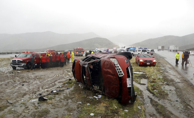 An overturned vehicle is seen at a scene of a fatal accident, where a volunteer member of the Ventura County search and rescue team was killed, along Interstate Highway 5 south of Pyramid Lake, Calif. Saturday, Feb. 2, 2019. The second in a string of powerful storms is battering California, bringing down trees, flooding roadways and prompting evacuations in wildfire burn areas where intense downpours could loosen bare hillsides and cause mudslides. [Photo: AP]