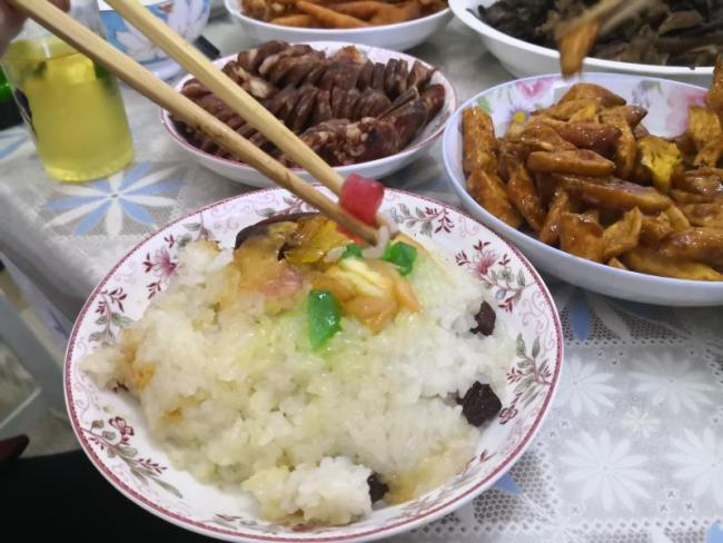 """""""Eight-treasure rice pudding,"""" Babaofan in Mandarin, is a combination of sticky rice, sugar, red dates and raisins. The traditional dish is popular across the country. It is said to embody auspiciousness, peace and happiness for the coming year. [Photo: China Plus/Guo Yan]"""