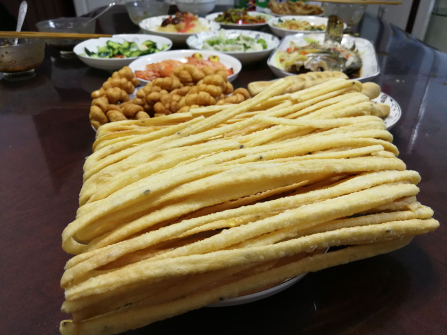 Sanzi, a fried dough twist, set out for a New Year's dinner in Lanzhou, Gansu Province, February 4, 2019. Fried dough twists are a traditional food in northwest China, where locals generally eat flour-based pastries ahead of the Lunar New Year. [Photo: China Plus/Sang Yarong]