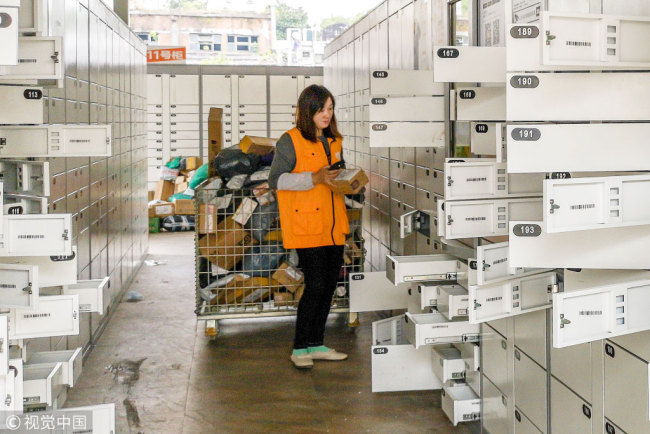 An employee puts parcels into self-service package lockers at a delivery service center at a university in Shanghai. [Photo: VCG]