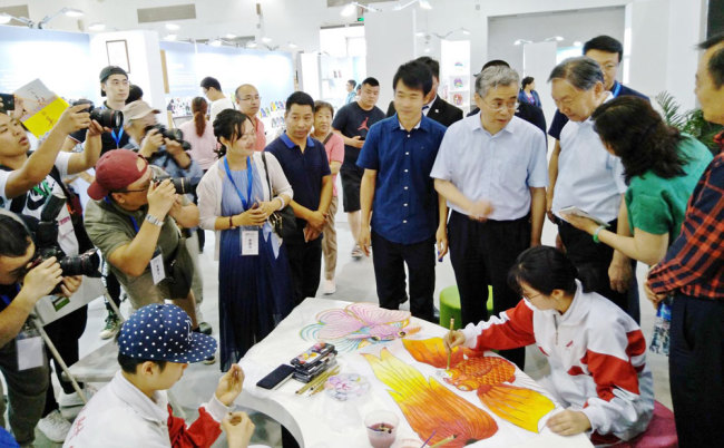 "China's Minister of Culture and Tourism Luo Shugang and Deputy Minister Xiang Zhaolun along with officials from the Beijing municipal government visit the booth for the High School Affiliated to Renmin University of China during the fourth Beijing-Tianjin-Hebei Intangible Cultural Heritage Exhibition. The students were making ""Cao's kites"" at the event in Beijing in June 2018. Cao's kite is named after Cao Xueqin, the author of Chinese classic ""Dream of the Red Chamber"". [Photo provided to China Plus]"