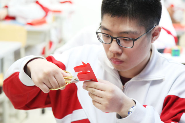 A student practices paper-cutting during an elective class on the traditional art form at the High School Affiliated to Renmin University of China in Beijing on Thursday, March 7, 2019. [Photo: China Plus]