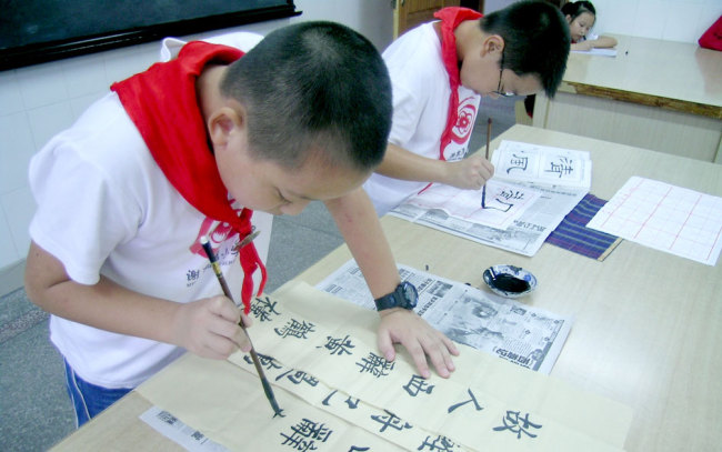 Pupils at Xiejiawan Primary School in Chongqing practice Chinese calligraphy. [Photo provided to China Plus]