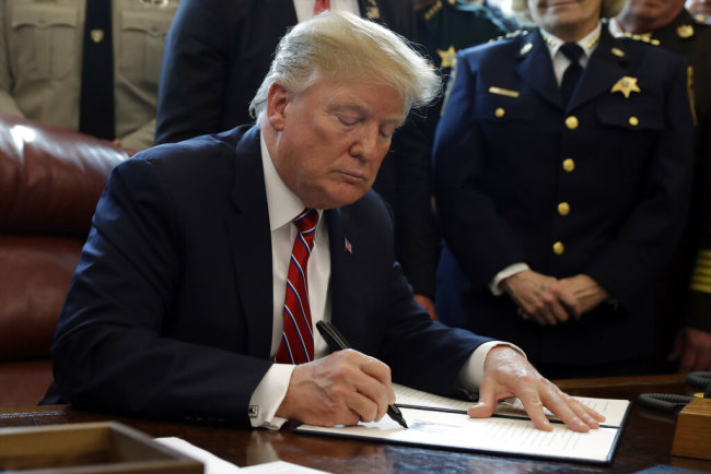 U.S. President Donald Trump signs the first veto of his presidency in the Oval Office of the White House, Friday, March 15, 2019, in Washington. Trump issued the first veto, overruling Congress to protect his emergency declaration for border wall funding. [Photo: AP/Evan Vucci]