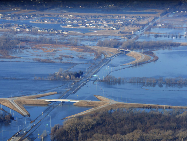 CORRECTS MONTH TO MARCH NOT MAY - The Elkhorn River consumes a section of western Douglas County Sunday, March 17, 2019, in Omaha, Neb. Hundreds of people were evacuated from their homes in Nebraska and Iowa as levees succumbed to the rush of water. [Photo: AP]