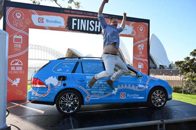 "Dutch driver Wiebe Wakker (C) celebrates after driving his retrofitted station wagon nicknamed ""The Blue Bandit"" onto a platform to complete a round-an-world trip in an electric car with a backdrop of Sydney Harbour Bridge in Sydney on April 7, 2019. Wakker drove some 95,000 kilometres across 33 countries in what he said was the world's longest-ever journey by electric car. [Photo: AFP/Peter Parks]"