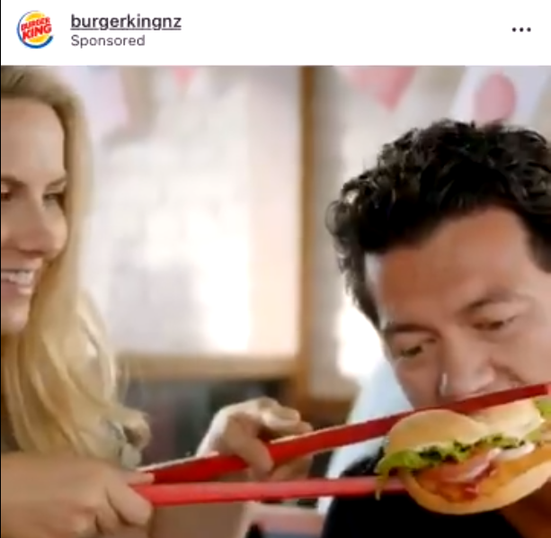 A screen shot from Twitter shows the video ad published by Burger King showing a customer eating a hamburger with oversized chopsticks. [Photo: thepaper.com]