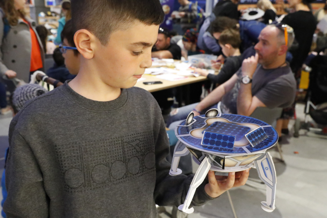 An Israeli boy plays with a model of the Israeli spacecraft Beresheet's, at the Planetaya Planetarium in the Israeli city of Netanya, on April 11, 2019 before it crashed during the landing.[Photo: AFP/JACK GUEZ]