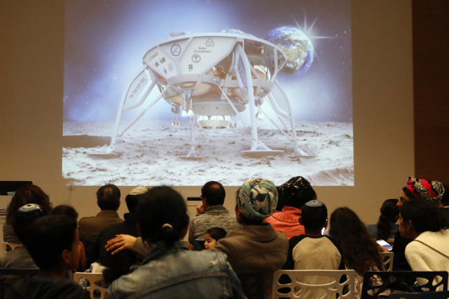 People watch a screen showing explanations of the landing of Israeli spacecraft, Beresheet's, at the Planetaya Planetarium in the Israeli city of Netanya, on April 11, 2019 before it crashed during the landing.[Photo: AFP/JACK GUEZ]