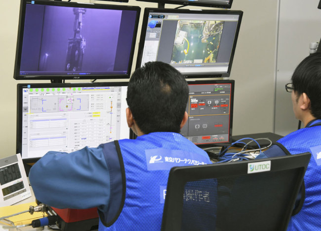 Tokyo Electric Power Co. workers remotely make operation for removing fuels at Unit 3 of Fukushima Dai-ichi nuclear plant, in Okuma, Fukushima Prefecture, northeastern Japan Monday, April 15, 2019. [Photo: Kyodo News via AP]
